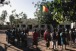 Raising the flag before school in the village of Kouakourou, Mali. From coverage of revisit to Material World Project family in Mali, 2001.