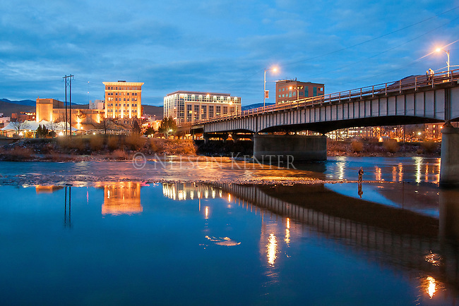 Missoula Montana downtown area viewed from across the Clark Fork River. Lights of the downtown area at dusk. The Wilma building, the Centennial building and the First Interstate Bank building. A fisherman in the waters of the Clark Fork River.
