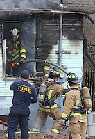 NWA Democrat-Gazette/DAVID GOTTSCHALK   City of Fayetteville firefighters retrieve a water hose from a structure fire Monday, February 13, 2017, at the intersection of East 9th Street and South College Avenue. The Fayetteville Fire Department reported that one person sustained minor injuries from the fire.