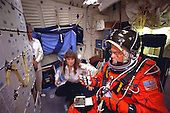 United States Senator John H. Glenn Jr. (Democrat of Ohio) prepares to rehearse launch readiness procedures on the mid deck of a crew trainer at the Johnson Space Center (JSC) in Houston, Texas on April 28, 1998. Sharon Jones, involved in crew training, briefs the STS-95 payload specialist. When he lifts off aboard the Space Shuttle Discovery in October of this year and later lands in Florida, Sen. Glenn will be seated in a temporary mid-deck chair like the one used in this training exercise.   .Credit: Joe McNally, National Geographic, for NASA via CNP