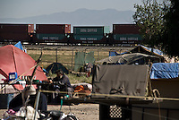 Camp Hope, eine Zeltstadt fuer Obdachlose in Ontario, Kalifornien.Containern der Firma China Shipping rollen auf Zuegen am Camp vorbei..Fotos © Stefan Falke..Camp Hope, a  tent city for the homeless in Ontario, California.Trains with containers bearing the sign China Shipping are passing by the camp.
