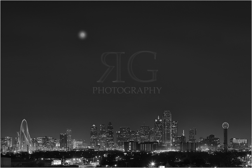 In black and white - On a cold December evening with the moon rising into the night sky, the Dallas skyline comes alive with color. From left to right, the architecture of Dallas offers the Margaret Hunt Hill Bridge, the Trammell Crow Tower, the Fountain Place, Lincoln Plaza, the Harward Center, Energy Plaza, the Renaissance Tower, the Bank of America Plaza, the CoAmerica Bank Tower, the Hyatt Regency Dallas,  the iconic Reunioin Tower, and the Omni Hotel Dallas (the blue and red building). Also, the full moon rising over the city peaked through the low clouds...Thanks to the Belmont Hotel for provided this vantage point. They were great to work with.