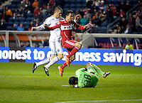 Chicago midfielder Marco Pappa (16) and Vancouver defender Greg Janicki (14) leap over sliding Vancouver goalkeeper Jay Nolly (18).  The Chicago Fire tied the Vancouver Whitecaps 0-0 at Toyota Park in Bridgeview, IL on May 7, 2011.