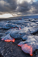 Visitors marvel at the glowing molten lava flowing down the hill at Hawai'i Volcanoes National Park, Hawai'i Island.