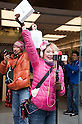 March 16, 2012, Tokyo, Japan - This woman happy to have bought the new iPad comes out of the store with your new tablet in hand, whiles records the event with her iPhone. .Fans lined up overnight outside the Apple store in Ginza, to buy the new iPad. Japan was one of the first countries where Apple fans could get their hands on the new iPad.