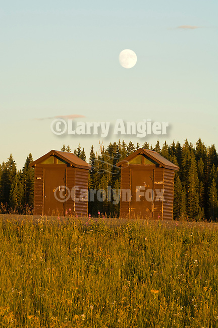 A waxing moon rises above twin brown outhouses on Grand Mesa in the Colorado Rockys