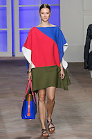 Jac walks the runway in a blue/pink/white/olive patchwork cotton button shoulder poncho, and blue/aqua/yellow striped bikini bottom, by Tommy Hilfiger for the Tommy Hilfiger Spring 2012 Pop Prep Collection, during Mercedes-Benz Fashion Week Spring 2012.