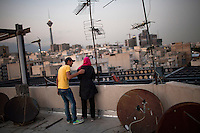 A couple smoke on a roof, surrounded by satelites hidden from view from the ground as satelite televison is banned.
