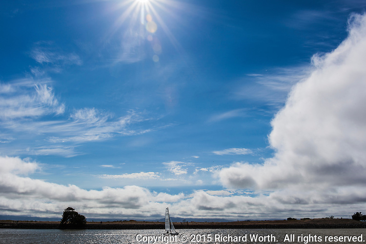A sunburst silently explodes in a blue cloud-filled sky over a quiet day sailing at the marina.