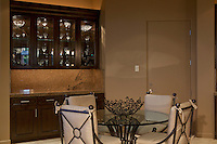 Small wrought iron and glass dining table is seen against glass cabinet