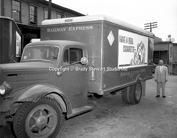 Pittsburgh PA:  View of Railway Express Marketing Manager standing next to a truck with advertising on it - 1957.  The new advertising approach was a direct result of the company's financial problems during the 1950s.  Railway Express was a group of private transportation companies throughout the Pittsburgh area. Due to continued financial problems, Railway Express was taken over by the state in 1964 and the emerging company was called the Port Authority of Allegheny County.