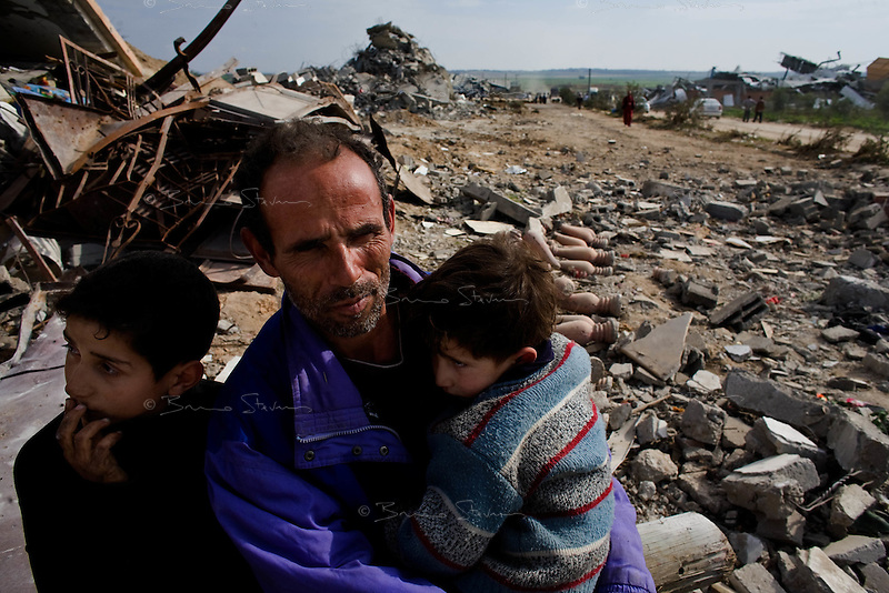 Al Tufa'ah, Gaza Strip, Jan 20 2009.Ibrahim Mohammed Hamouda conforts his sons Saher Brahim, 3, right and Wasim, 8, left, on the ruins of their family home. Hundreds of houses, farms and factories have been destroyed and bulldozed over by the Israeli army, flattening approximately an area 10km square, ruining countless families, left resourceless in what amounts to collective punishment..