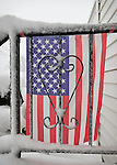 Merrick, New York, U.S. February 13, 2014 - As yet another snow storm slams into Long Island, a snowy American Flag decorates the unshoveled front stoop of a suburban home. Gov. Cuomo declared a state of emergency for L.I. and much of the state, and 5 to 14 inches of snow are expected to fall on Nassau and Suffolk Counties through to the evening,