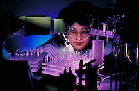 A lab tech watches as robot fills test tubes in drug experiments. Lab Technician.