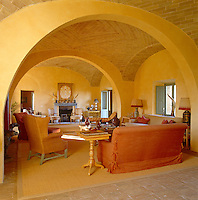 Beneath an ancient brick vaulted ceiling tones of gold and orange suffuse the drawing room