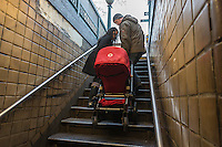 A couple carries a stroller up the stairs as they exit the subway in Chelsea in New York on Saturday, December 29, 2012. (© Richard B. Levine)