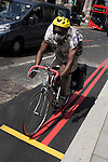 Cyclist speeds through the City of London, his bike and helmet matching the yellow and red lines on new tarmac.