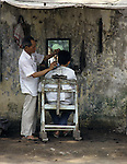 A customer receives a hair cut from a street side barber in Hanoi, North Vietnam.  (Jim Bryant Photo).....