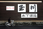 A girl cycles past the Tamagawa Sake Brewery in Kyoto, Japan. The traditional market for sake is literally dying offand the supply side is fading too, as old masters retire without a new generation to take over the brewing vats. Photographer: Robert Gilhooly