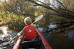 Rear view of a boy kayaking on Concord River in the fall.