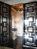 Art Deco-inspired double entrance doors in black lacquer and brushed stainless steel set the tone of the apartment