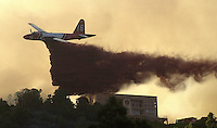 "A ""slurry bomber"" firefighting airplane drops a load of fire retardent to stop the Ute Pass Fire near a home north of Durango, Colorado in June, 2002."