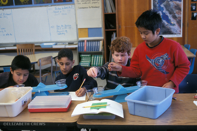 Berkeley CA 5th grade boys working on science investigation in class, learning ways to measure and weigh