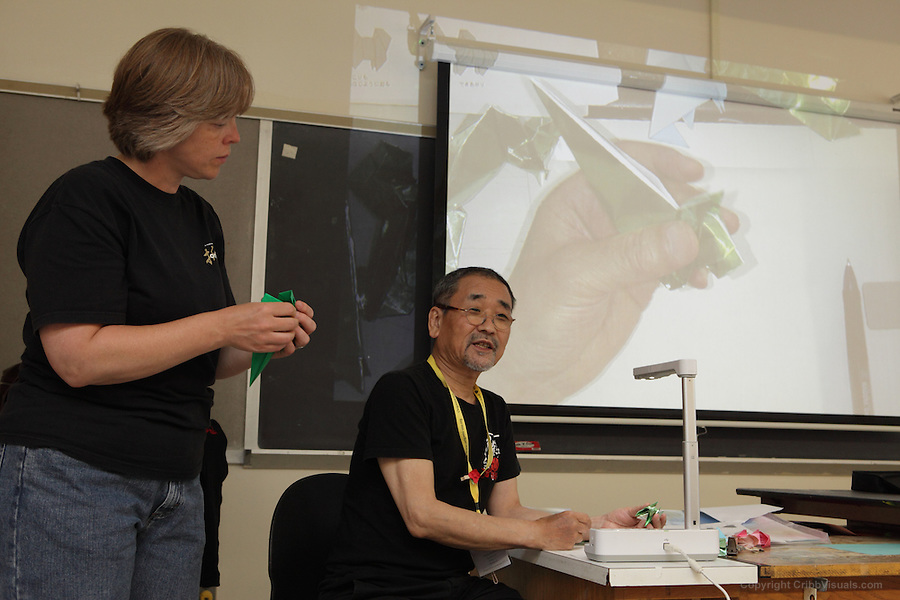 New York, NY, USA - June 24, 2012: Makoto Yamaguchi, Japan, teaches Cute Animals, elegant origami models of his own design to a class at the OrigamiUSA 2012 Convention held at Fashion Institute of Technology, New York. Anne LaVin translated from Japanese.