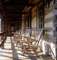Weathered rocking chairs on the porch blend with the log and plaster walls of this log cabin