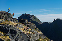Two female hikers on summit on Nonstind mountain peak, Moskenesøy, Lofoten Islands, Norway