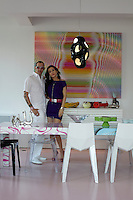 Karim Rashid and his wife Ivana standing in front of a colourful psychedelic artwork in the dining area of their New York apartment