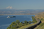 Barge on Columbia River with train running besides the river with Mt Adams in background