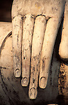 The hands of a Buddha statue in Sukhothai Historical Park point to the ground in a pose known as 'calling the earth to witness'.
