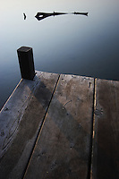 Driftwood floats on calm lake water beyond the edge of a boat dock