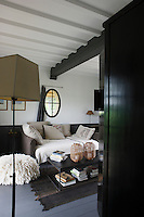 The bedroom is lit by an oval oeil-de-boeuf style window and the bedding is a restful neutral linen