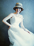 A woman in a  white dress & a straw hat, seated by a plain background, ina  joyful expression, smiling.