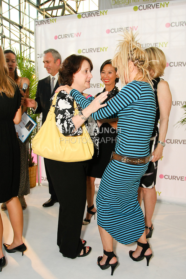 Andrea Goldsmith speaks with Betsey Johnson after winning a trip to Paris during the charity raffle at the CURVE and CFDA Party For A Cause event during the CURVENY Lingerie & Swim show, at the Jacob Javits Convention Center, August 2, 2010.