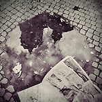an old church reflected in a puddle with an old newspaper