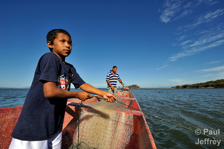 12-year-old Jorge Osorio helps his father Danilo fish off the coast of Honduras in the Gulf of Fonseca. Along with other families in their village, they have lost access to some land and parts of the ocean in recent years as the wealthiest family in Honduras has moved in, fencing off vast areas.