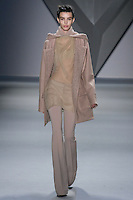 Kate King walks runway in a nude melton wool oversized parka with boucle lining and detachable hood over nude silk chiffon cowl neck halter top and silk chiffon bra, with nude techno stretch flared pant, from the Vera Wang Fall 2012 Vis-a-gris collection, during Mercedes-Benz Fashion Week Fall 2012 in New York.