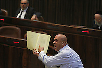 Knesset member Basal Getas from the Balad party points at empty pages as he holds up a copy of the state budget proposal during a plenum session voting on the state budget, in the Knesset, Israel's Parliament, in Jerusalem, late night July 29, 2013. The Knesset approved the State Budget at second and third readings in the early hours of Tuesday morning in a 58-43 vote, following a 15-hour parliamentary session. Photo by Oren Nahshon