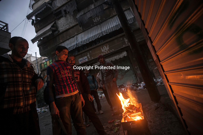 In this Tuesday, Dec. 04, 2012 photo, night falls in Sucari neighborhood as Syrian residents use fire to keep them warm in Aleppo, the Syrian's largest city. (AP Photo/Narciso Contreras)