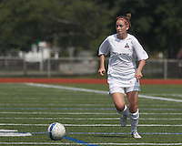 Boston Aztec defender Amanda Rumsey (16) brings the ball forward.  In a Women's Premier Soccer League (WPSL) match, Boston Aztec (white) defeated Seacoast United Mariners (blue), 2-1, at North Reading High School Stadium on Arthur J. Kenney Athletic Field on on June 23, 2013. Due to injuries through the season, Seacoast United Mariners could only field 10 players.