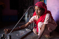 Suki (not her real name), spins cotton in her house in Jhaju village, Bikaner, Rajasthan, India on 4th October 2012. Now 20, Suki was married off at age 12, but only went to live with her husband when she was 14. The three sisters, aged 10, 12, and 15 were married off on the same day by their maternal grandfather while their father was hospitalized. Her husband died three years after she moved in, leaving her with a daughter, now 6, and a son, now 4. She has no parents-in-laws and thus returned to her parents house after being widowed because her brother-in-law, who had become the head of the family after his brother's death, had refused to allow Suki to inherit her deceased husband's fair share of agriculture land. Although Suki's father wants her to remarry, she refuses to, hoping instead to be able to support her family through embroidery and tailoring work. The family also makes hand-loom cotton to subsidize their collective household income. Photo by Suzanne Lee for PLAN UK