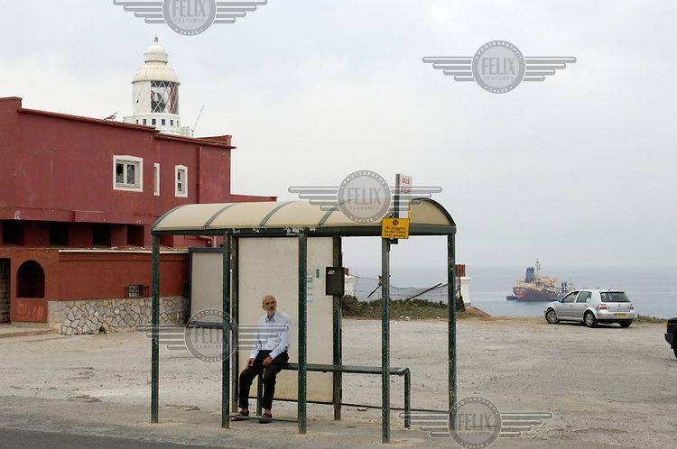 A man waits for a bus by the Europa Point lighthouse, the southern-most tip of Gibraltar.