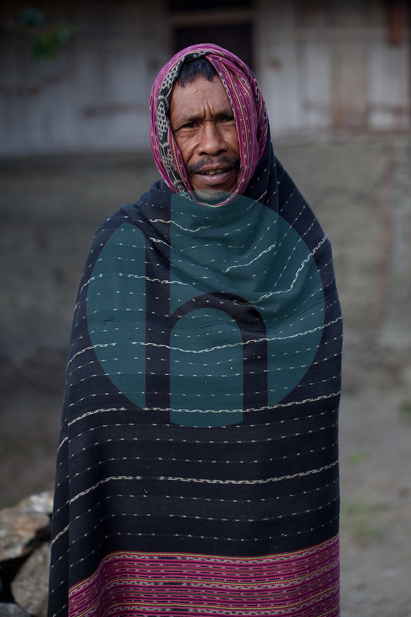"To protect himself from the cool morning air, a man wraps himself in a locally woven fabric known as ""Tais"" in the mountain town of Laclubar, Timor-Leste on Wednesday, Oct. 19th, 2011.  Photographer: Daniel J. Groshong/The Hummingfish Foundation"