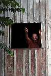 South America, Brazil, Amazon. An Amazon resident reaches out to greet passers by on the river.