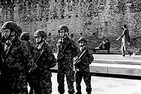 """Switzerland. Canton Ticino. Bellinzona. Piazza del Sole. A group of men from the Swiss Armed Forces, all wearing camouflage uniforms and carrying automatic or semi-automatic assault rifle SG 550. A woman reads a book seated on a bench while two men walk by castle's wall. The SG 550 is an assault rifle manufactured by Swiss Arms AG (formerly a division of Schweizerische Industrie Gesellschaft now known as Sig Holding AG) of Neuhausen, Switzerland. """"SG"""" is an abbreviation for Sturmgewehr, or """"assault rifle"""". The rifle is based on the earlier 5.56mm SG 540 and is also known as the Fass 90 (Fusil d'assaut 90/Fucile d'assalto 90) in French/Italian or Stgw 90 in German (Sturmgewehr 90). 11.04.2017 © 2017 Didier Ruef"""