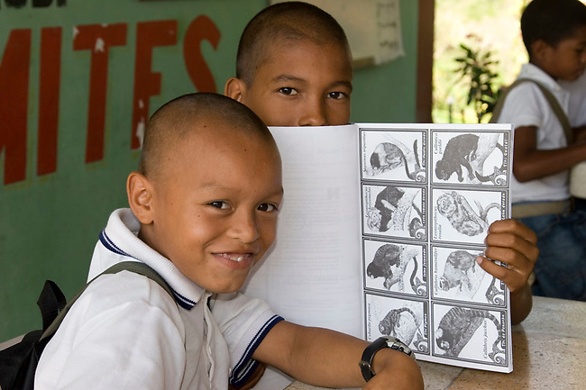 Colombian students proudly display educational material designed to teach them about primates in their forests. Los Limites, Colombia.