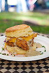 "Pine State Biscuits in Portland, OR at the Saturday Farmers' Market in the South Park Blocks in Portland State University's Campus.. The ""Reggie Deluxe"" - a buttermilk biscuit with fried chicken, Tillamook cheddar cheese, bacon, a fried egg, all toopped with home made gravy."